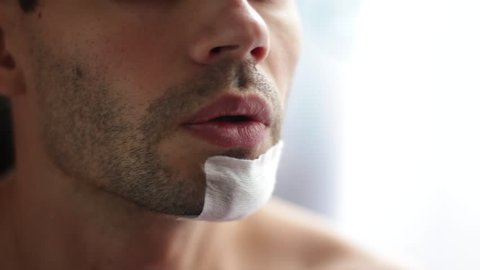 replace the bandage on the wound on his face. Women's hands tear off the band-aid from the patient's face. Dressing of a torn wound on the face.