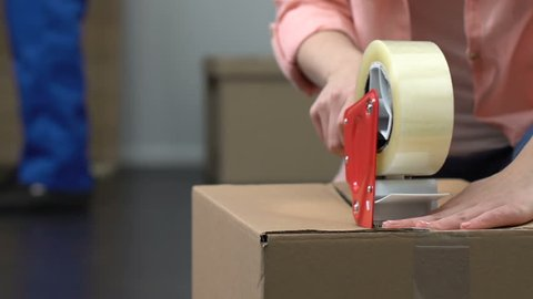 Girl packing stuff in box, moving, delivery service worker helping on background