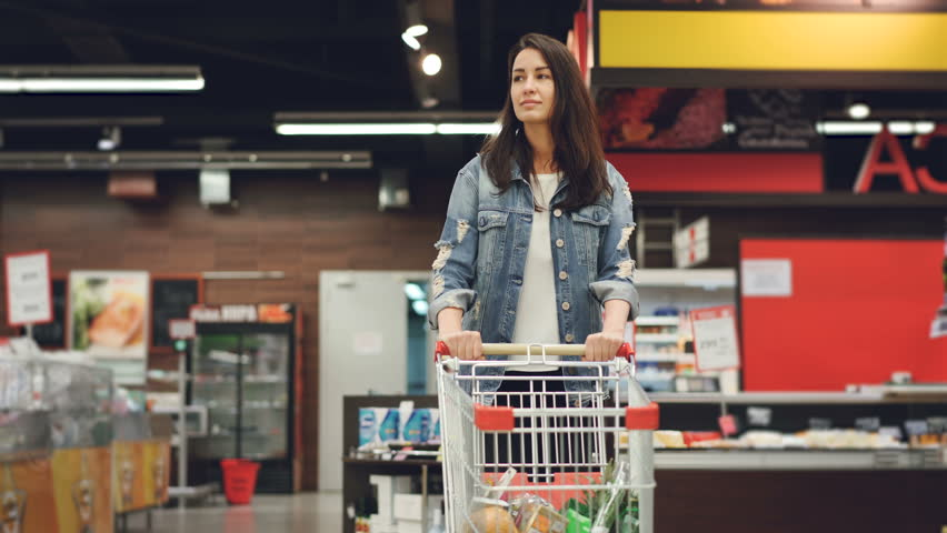 Pretty lady in casual clothes is walking in grocery store steering shopping trolley with food inside it and looking around at shelves with products. Women and shops concept. | Shutterstock HD Video #1012263629