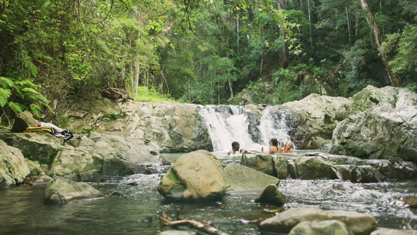 Guys jumping into water and swimming with friends near waterfall in rainforest. Shot with RED camera. 4k footage.