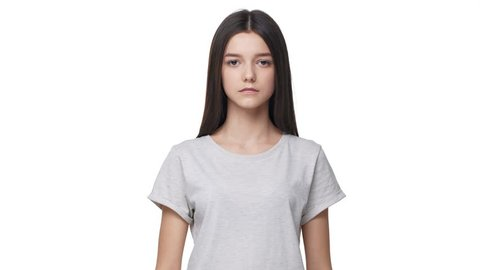Portrait of beautiful teen girl in basic t-shirt smiling at camera and touching her long dark hair, isolated over white background in studio. Concept of emotions