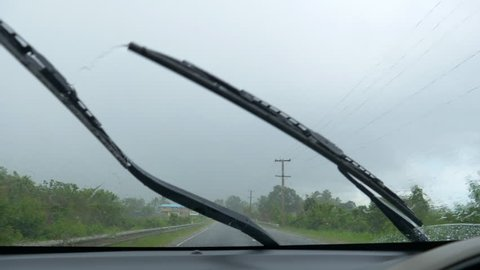 SLOW MOTION, FPV: Tranquil countryside of Cook Islands gets caught in a rainstorm. Windscreen wipers can barely keep up with the monsoon rain during wet season as car drives along an empty rural road.