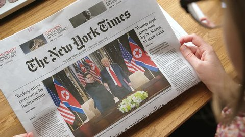 PARIS, FRANCE - JUNE 13, 2018: Woman reading The New York Times newspaper in the office showing on cover U.S. President Donald Trump meeting North Korean leader Kim Jong-un in Singapore