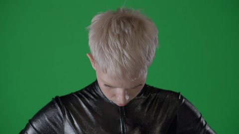 Blonde girl with short hair and furious sight is looking at camera. Transgender human is posing in a green-screen, looking around
