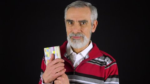 An elderly man holds a book, smiles at it and at the camera - black screen studio