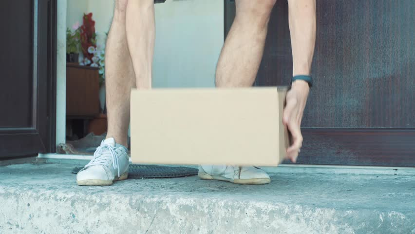A man picks up a package from outside his front door