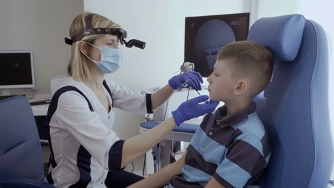 Doctor examine nose of little boy with otoscope