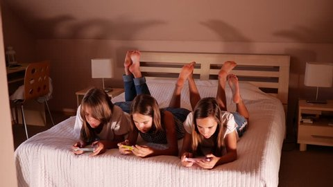 Type use smart phones chatting in social media three girls teenager sisters at home on bed in evening