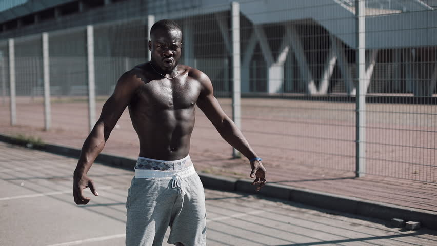 Athletic African American man with a bare torso posing shows his muscles outdoors. Black man posing near the stadium, shows his muscles. Bodybuilding, posing, health, fitness, beauty.