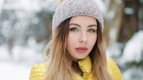 14de54835e1 Charming woman with blue eyes stands in winter hat in the forest covered  with snow.