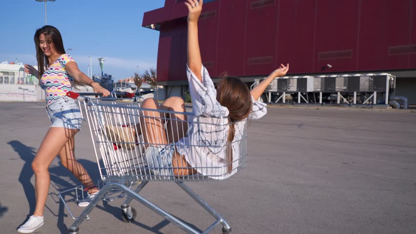 Girls playing with shopping cart. Two young women spinning and playing with pushcart on an empty parking lot.