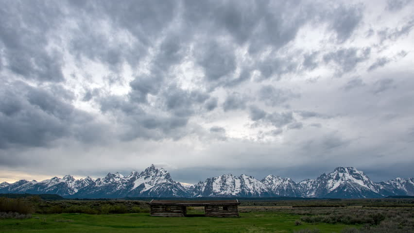 Time lapse overlooking the Grand Teton Mountains above the Cunningham Cabin in the evening on a cloudy day.