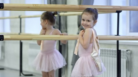 Medium shot of adorable little girl in pink leotard and tutu skirt carrying pointe shoes and running towards ballet barre in dance studio, then looking at camera and smiling