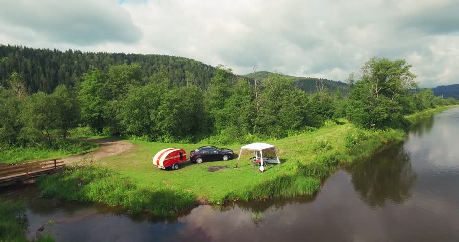 Family Car Camping with Residential Trailer and Tent on the River Coast in a Wild Bautiful Place in Ural Mountains - Aerial Drone View