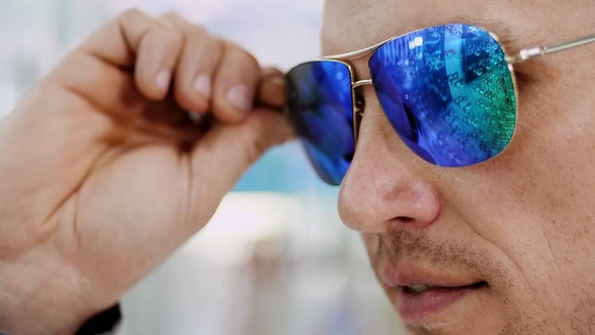 close-up, portrait of Handsome young man trying on blue sunglasses at optical store, optician retail store. in glasses of spectacles is reflected the showcase of optics with glasses