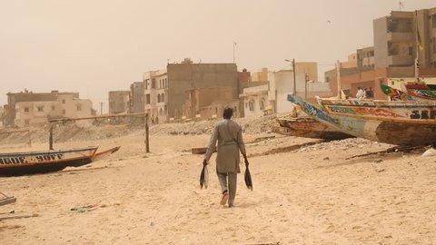 Africa: man walking down the beach with big fish in Dakar, Senegal.