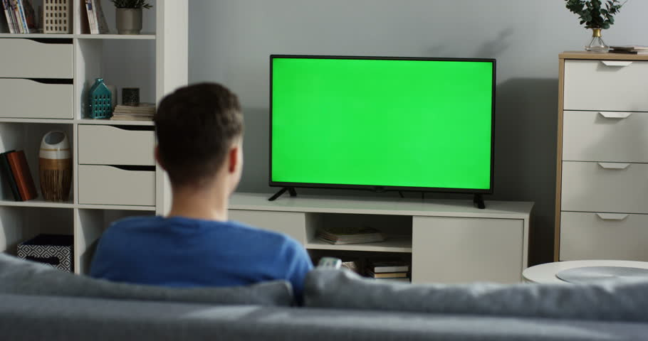 Back view on the young man sitting on the couch in the living room, watching TV with green screen and changing channels with a remote control in his hand. Chroma key. TV in focus. Indoor | Shutterstock HD Video #1012385369