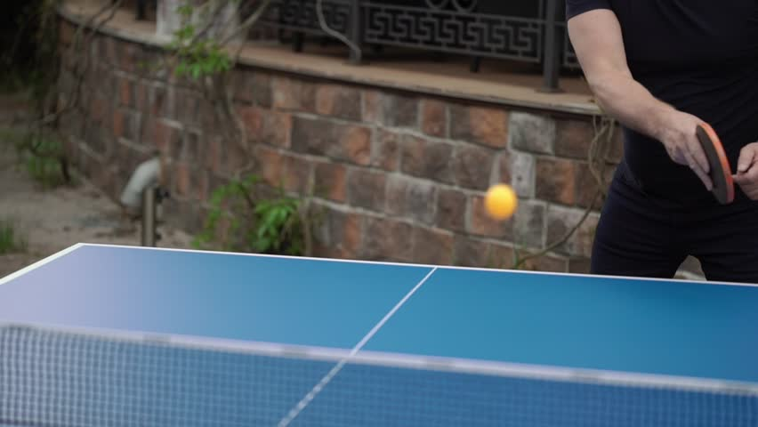 People playing table tennis outdoors