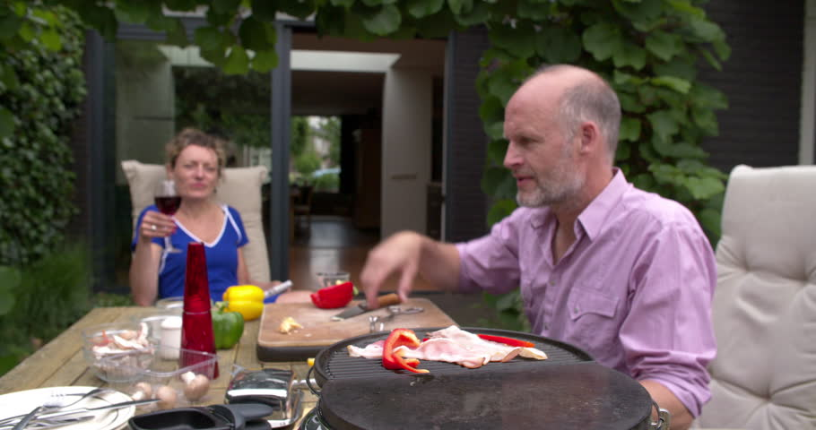 Man cooking at home in garden outdoor and toasting with his wife who drinks red wine.