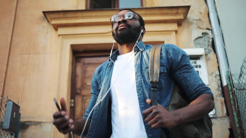 ?frican American young attractive man with glasses using phone walk on street listens to music in headphones smile sunlight sunset cellphone fashion internet face outside technology black city mobile | Shutterstock HD Video #1012425029