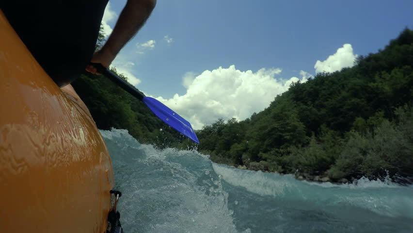 Person Paddling Through White Water Rapids.  Paddle, river and the side of the boat during white river rafting. Extreme and fun sport . Extreme Rafting on the Fast Mountain River, POV.