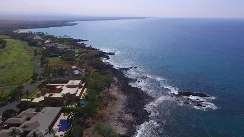 Luxury homes by the blue ocean. Green golf course, black lava rock and small waves on rocky beach. tropical view from above by drone. Kona coast and shoreline