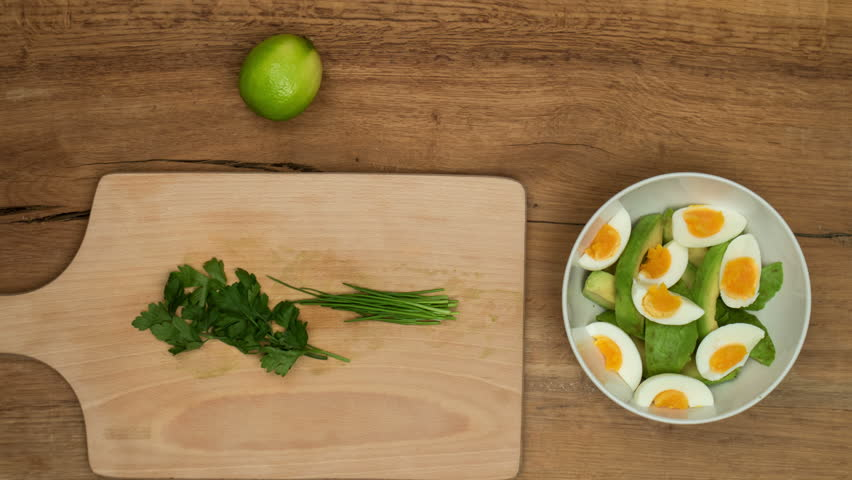 Avocado with Eggs salad. Top view on recipe preparation. Stop motion animation and timelapse eating.