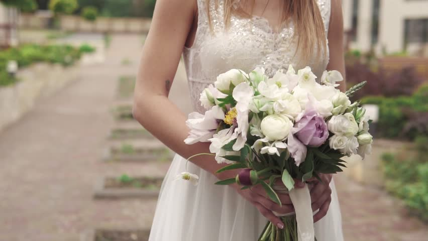 young girl in a wedding dress is holding a bouquet of the bride. Close-up. Wedding bouquet. Beautiful bridal bouquet in hands of young bride dressed in white wedding dress. slow motion.