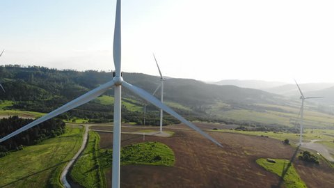beautiful green meadow with wind turbines converting kinetic energy into electrical