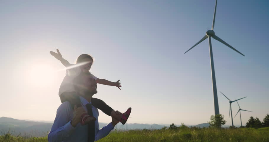A father engineer, holds his daughter in his arms and runs between the wind turbines with great freedom. Concept of: environmental engineering, renewable energy and love for nature and for the family