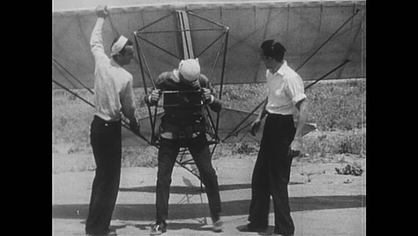 1950s: Man straps into glider, runs along field, falls down. Man pedals aircraft down ramp, lands on ground. Man pedals rocket bike, falls down, bike explodes. Man runs down lane with large wings.