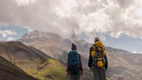 CINEMAGRAPH: Hiking People Looking At Mountain Clouds Timelapse. Couple Travelling. Hikers man and woman lovers trekking with backpacks in trail.