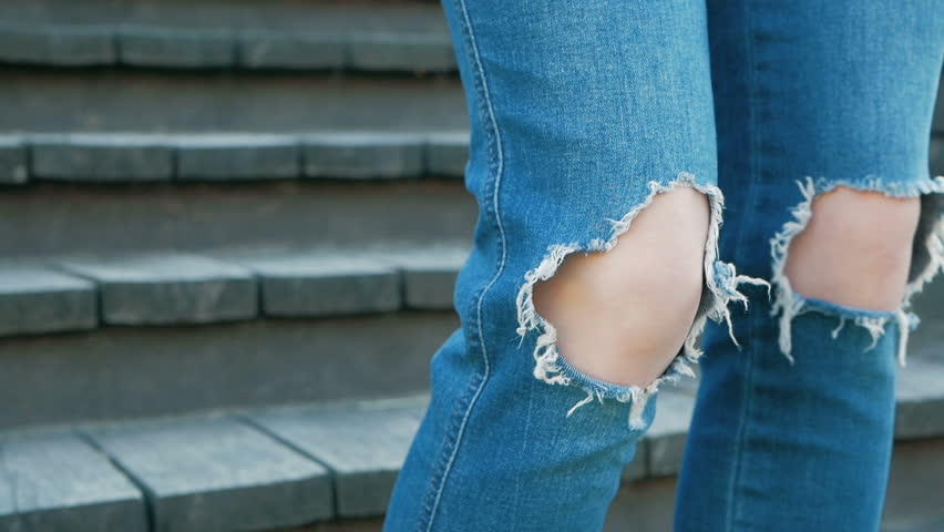 Knees of a girl in torn blue jeans. Teenager and fashion. Clothes for young people. Stylish denim pants with holes | Shutterstock HD Video #1012515839