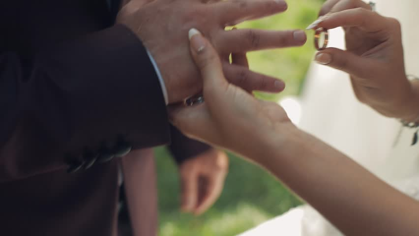 The bride puts on the wedding ring to the groom | Shutterstock HD Video #1012519109