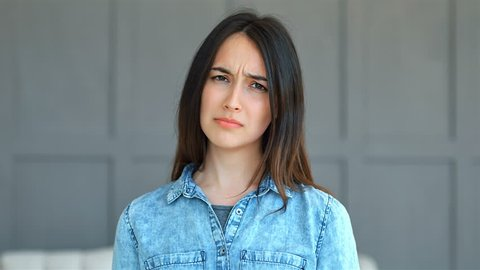Cranky young woman saying no, looking at the camera indoor