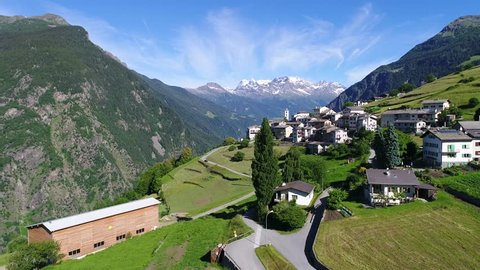 Village of Viano in Val Poschiavo. Aerial view. Green meadows and small village in Switzerland.