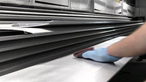Man smoothing a metal panel with an abrasive pad preparing for spraying