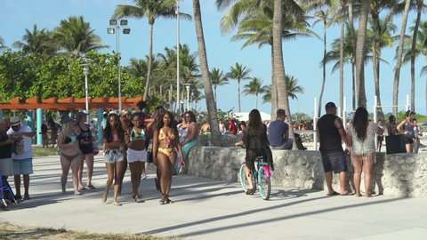 Miami beach cityscape, street view. South beach at spring break time. Crowd of students and tourists walking in the Lummus Park at Ocean drive - April 2018: Miami beach, Florida, US