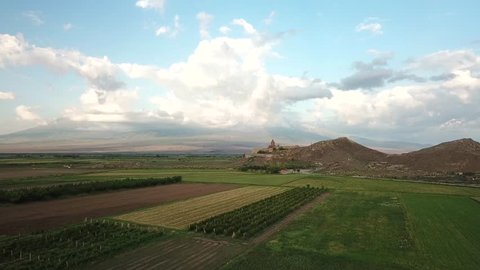 Aerial view of 17th century monastery Khor Virap from a drone flying over agricultural field on the border of Armenia next to Mt Ararat. Ararat Province, Armenia.
