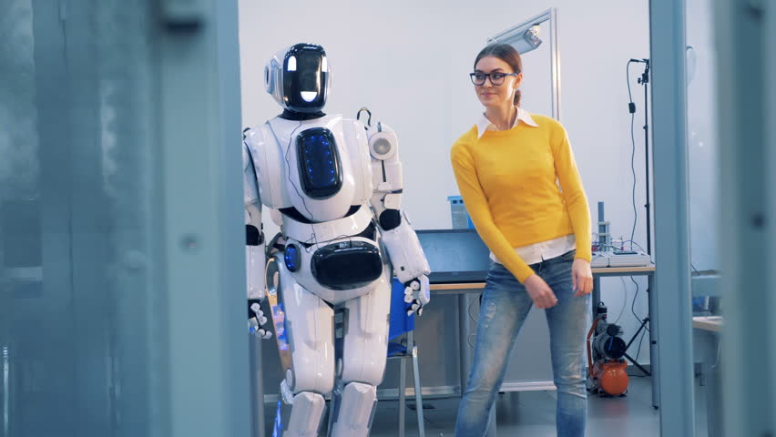 Robot and human relations. A cyborg spanks a woman, while dancing, then she slaps its face and leaves. 4K.