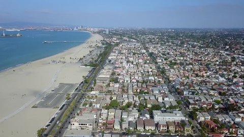 A smooth westerly flight of aerial drone footage over the Belmont Shore area of Long Beach, California, featuring coastal homes, views of the beach & sand, the pier, downtown Long Beach and Ocean Blvd