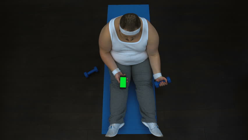 Lazy fat man lifting dumbbell and watching video on smartphone, burning calories | Shutterstock HD Video #1012573799