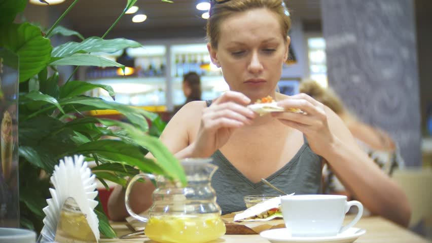 the woman is eating in the cafe quesadilla with chili and nachos. 4k, slow motion