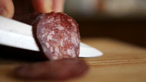 Man cuts into thin slices fatty sausage. Shooting closeup. Chef cutting salami with a knife on a wood board close up.