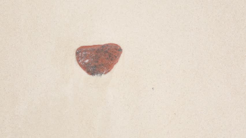 Top view of sea wave on the sand with stone with heart shape on the tropical beach, close-up