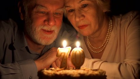 Loving senior couple celebrating anniversary with cake at home in evening. Happy elderly family hugging, cuddling together, make wishes and blowing out candles in form of number 70. Focus on seniors
