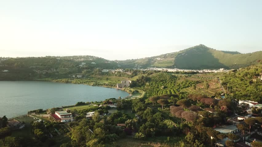Aerial drone flight over a volcanic crater lake, Lake Avernus (Lago d'Averno) in the south of Italy near Pozzuoli and Napoli.  It was considered the entrance to Hades in roman mythology,