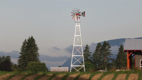 A tall, modern windmill in a rural setting quickly spins by a strong wind.