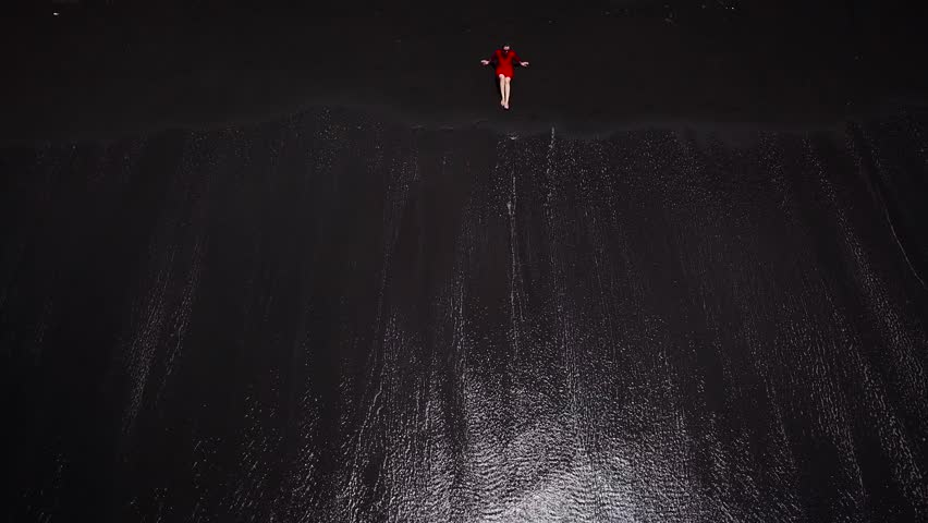 Aerial view of a girl in a red dress sitting on the beach with black sand. Tenerife, Canary Islands, Spain