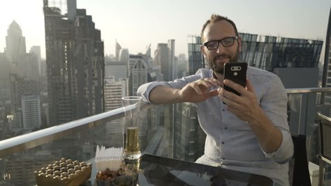 Man having a videocall on smartphone in skybar and drinks beer